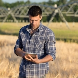 A stock image of a gentlemen checking his tablet while on an agricultural property